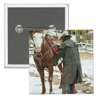 Man putting saddle on horse pinback button