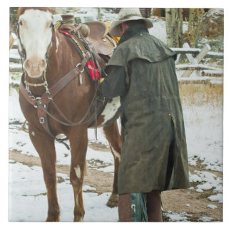 Man putting saddle on horse large square tile