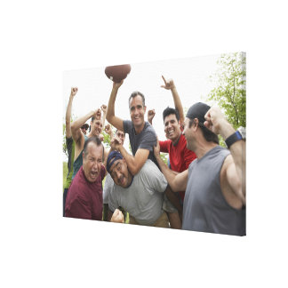 Man raising soccer ball celebrating with friends gallery wrapped canvas