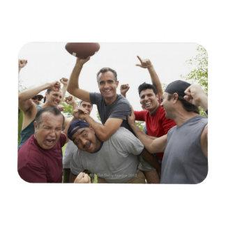 Man raising soccer ball celebrating with friends magnet