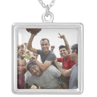Man raising soccer ball celebrating with friends jewelry