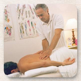 Man receiving massage beverage coaster