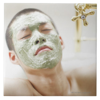 Man Relaxing in a Bathtub with a Facial Mask Ceramic Tile