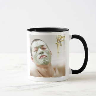 Man Relaxing in a Bathtub with a Facial Mask Mug