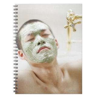 Man Relaxing in a Bathtub with a Facial Mask Notebook