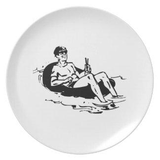 Man Relaxing in Inner Tube Plate
