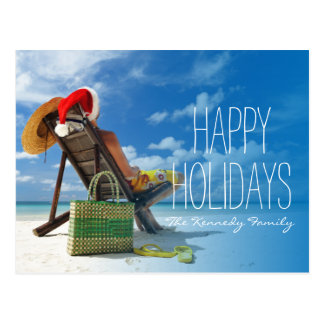 Man relaxing on the beach in santa's hat postcard