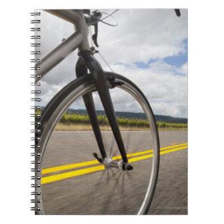 Man road biking at high speed POV Spiral Notebook