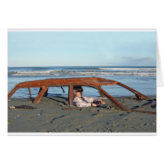 Man sitting in rusty car on beach card