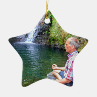 Man sitting on rock meditating near waterfall ceramic ornament