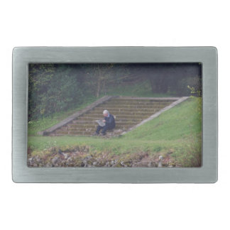 Man sitting on the steps reading a newspaper belt buckle