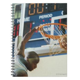 Man slam dunking basketball note books