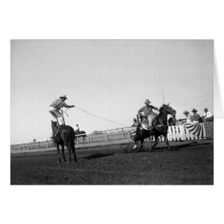 Man standing on a horse roping a horse and rider card