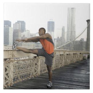 Man stretching on brooklyn bridge ceramic tile