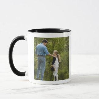 Man talking to girl in baseball uniform mug