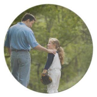 Man talking to girl in baseball uniform plate