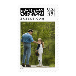 Man talking to girl in baseball uniform postage