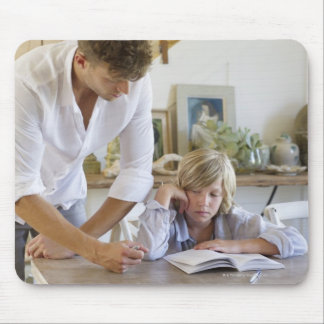 Man teaching his son at house mouse pad