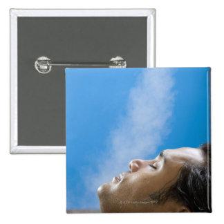 Man under steam faucet at spa pinback button
