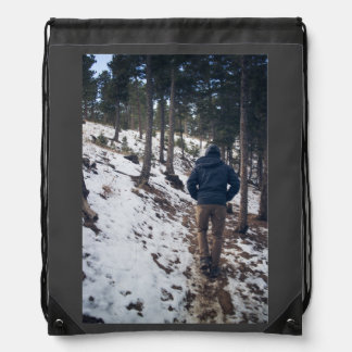 Man walking on a narrow passage drawstring backpack