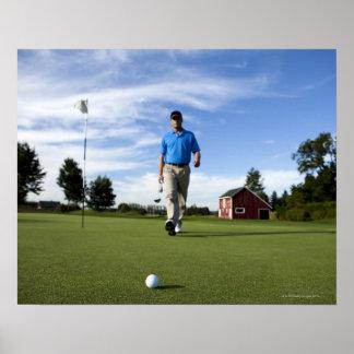 Man walking towards his golf ball. poster