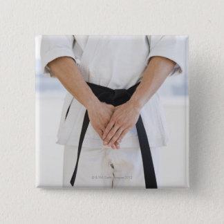 Man wearing karate black belt pinback button