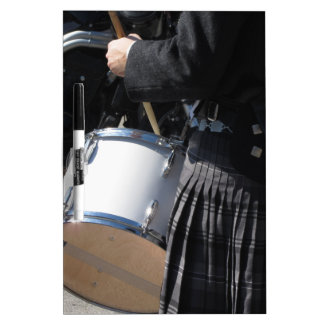 Man with kilt playing on drums dry erase board