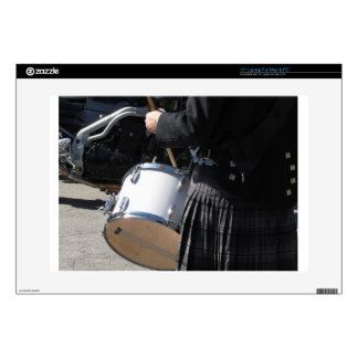 Man with kilt playing on drums skins for laptops