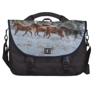 Manada de los caballos que corren en nieve del bolsa de ordenador