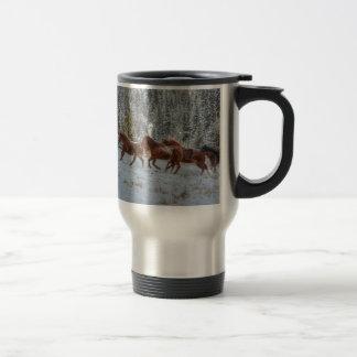 Manada de los caballos que corren en nieve del taza térmica