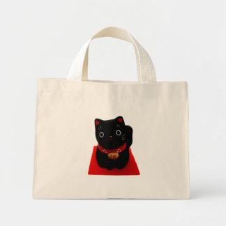 Maneki negro Neko en una alfombra roja Bolsa