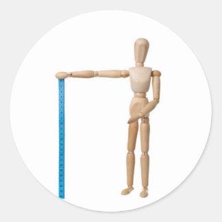 Maniquí que detiene a una cinta métrica pegatina redonda
