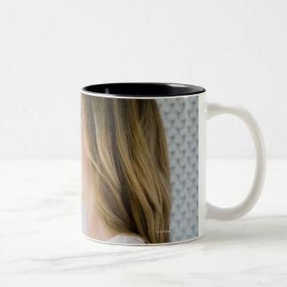 Mano abierta de la tenencia de la mujer a la taza de café de dos colores