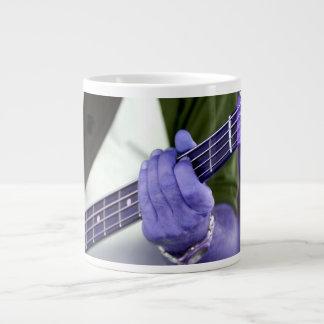 mano azul baja del jugador en la fotografía del taza de café gigante