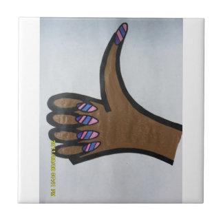 Mano con la mano manicured de los clavos en la tej azulejo cuadrado pequeño