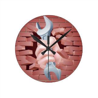 Mano de la llave inglesa que se rompe a través de reloj redondo mediano