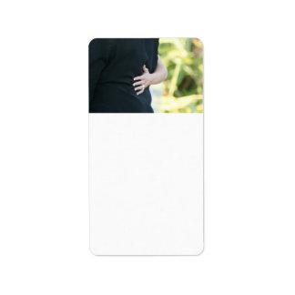 mano de la mujer en hombre negro de la chaqueta etiqueta de dirección