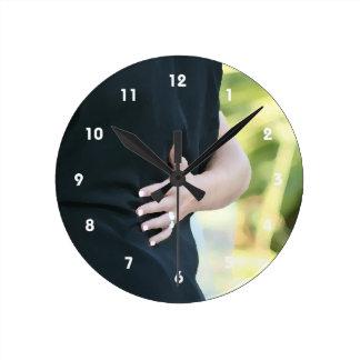 mano de la mujer en hombre negro de la chaqueta reloj redondo mediano