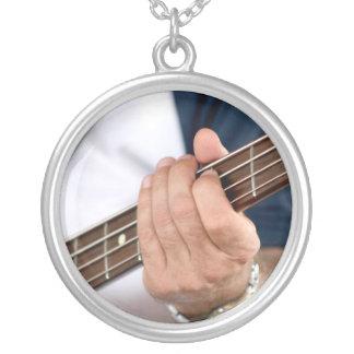 mano del bajista en el varón photograph.jpg del cu colgante redondo