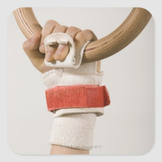Mano del gimnasta que lleva a cabo el anillo pegatina cuadrada