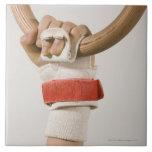 Mano del gimnasta que lleva a cabo el anillo teja