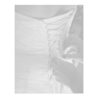 Mano femenina que ata encima del vestido de boda d membrete