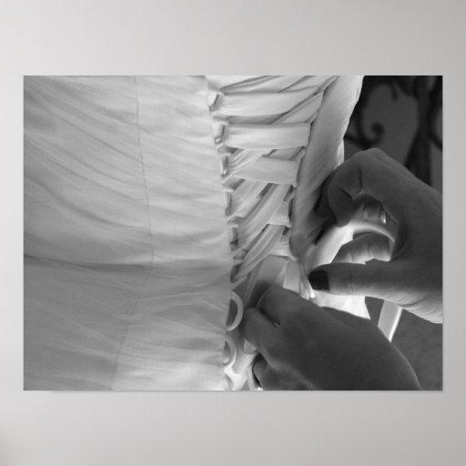 Mano femenina que ata encima del vestido de boda d póster