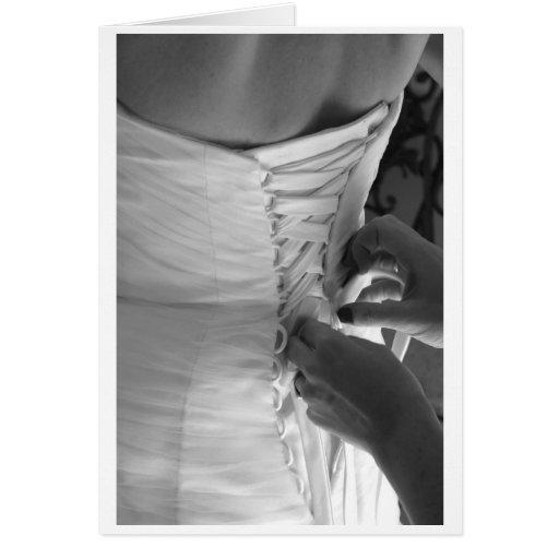 Mano femenina que ata encima del vestido de boda d tarjeta