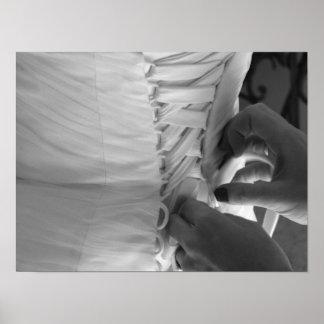 Mano femenina que ata encima del vestido de boda póster
