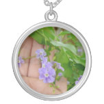 Mano, flores púrpuras, hojas colgante redondo