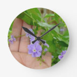 Mano, flores púrpuras, hojas reloj