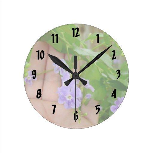 Mano, flores púrpuras, hojas reloj redondo mediano