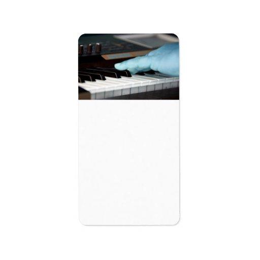 mano izquierda eléctrica azul del piano que juega  etiqueta de dirección