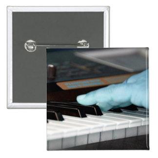 mano izquierda eléctrica azul del piano que juega  pin